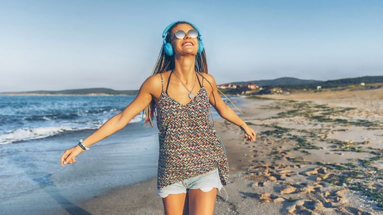 Cheerful young woman with blue headphones listening music on beach.
