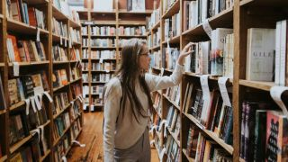 Person browsing books on a book shelf