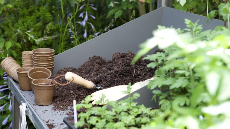 how to compost: tray of compost and plant pots ready for planting