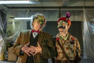 Steve Pemberton and Reece Shearsmith in character as The Doctor and Scaramouche in 'Wuthering Heist'. The Doctor wears a tweed jacket, a checked shirt, a red bow tie, a waistcoat and a green mask over the top half of his face. Scaramouche wears an army uniform with a red beret, and a green mask with a large nose over the top half of his face.