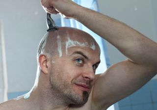 man shaving his head in the shower