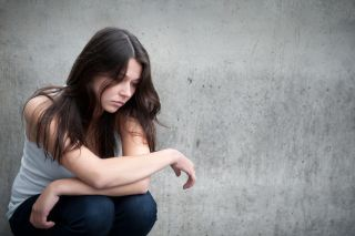 A teenage girl sits looking sad or in pain.