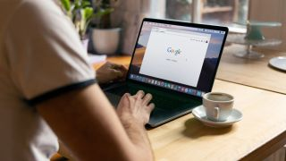person at desk on laptop accessing google