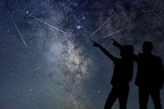 Silhouettes of people watching meteor shower.