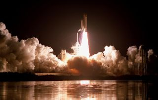 Like a rising sun, space shuttle Discovery rockets into the night sky on the STS-103 mission on Dec. 19, 1999 at 7:50 p.m. EST. The brilliant light creates a reflection of the launch in the water nearby. STS-103 was a servicing mission for the Hubble Spac
