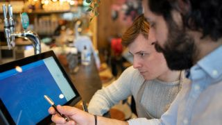 Two hospitality workers look at a POS system together