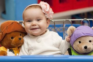 a baby between two teddy bears