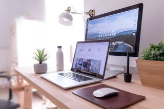 best web hosting - MacBook and iMac on desk in home office
