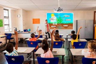 Kids in classroom raise hands while watching Epson projector