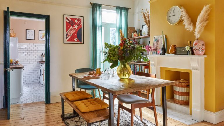 dining room with a mustard yellow feature wall, industrial style dining set and a large vase of flowers
