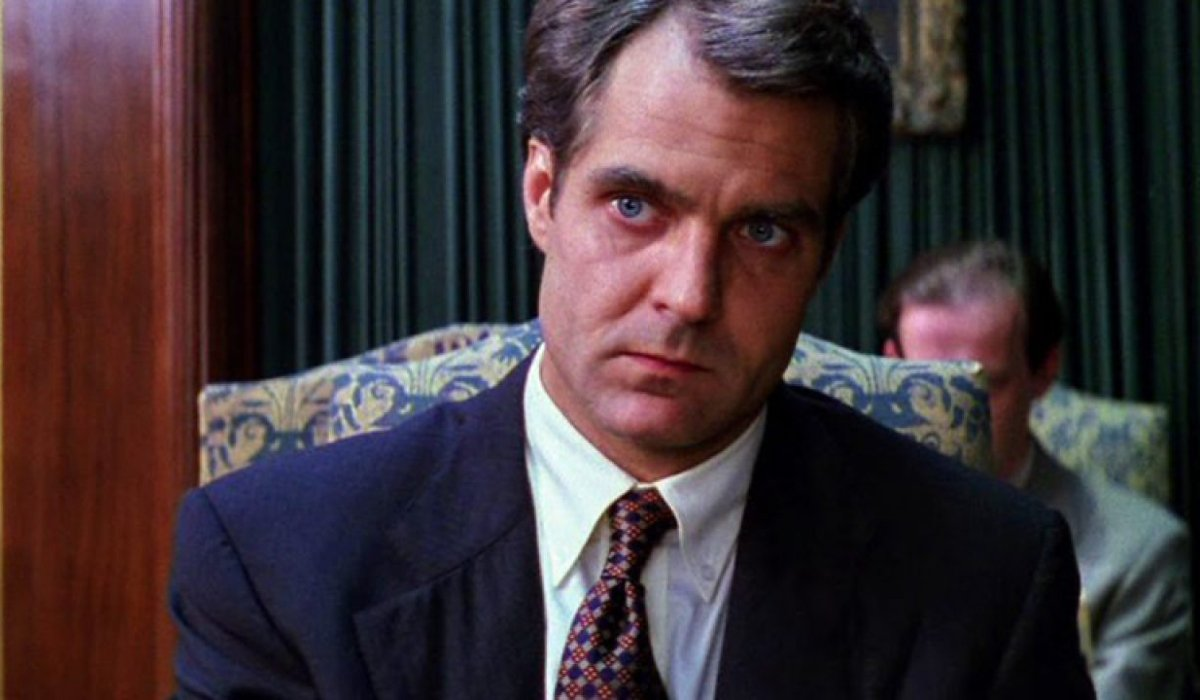 Henry Czerny sitting in a restaurant, looking concerned, in Mission: Impossible.