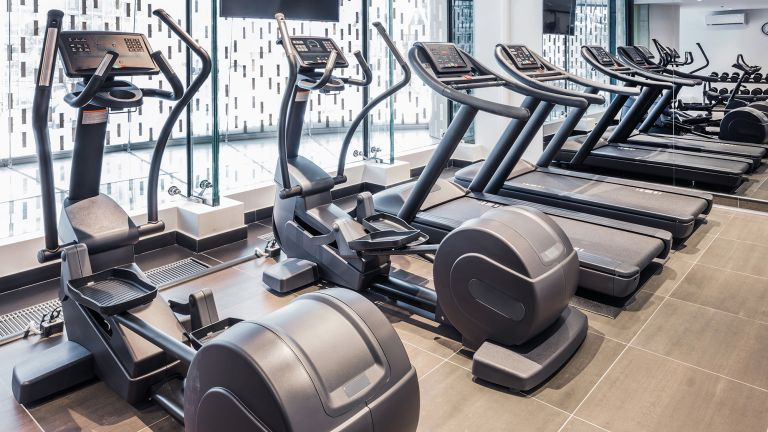 A variety of cardio machines including elliptical machines and treadmills in a gym