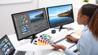 Download Premiere Pro - a woman using Premiere Pro on two monitors and a laptop