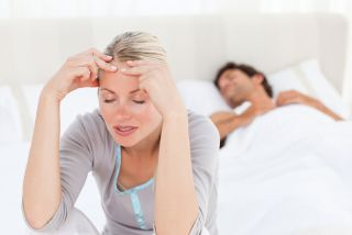 A woman rubs her head as if in pain, while her husband sleeps.