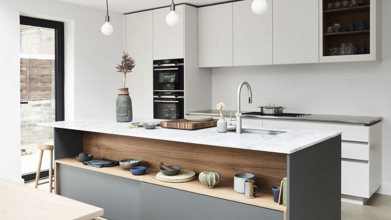 A modern kitchen with grey and wooden island with open shelving, and white handleless cabinetry