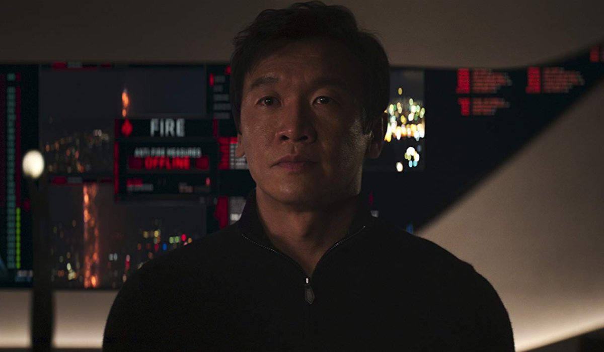 Skyscraper Chin Han stands in front of an important control panel.