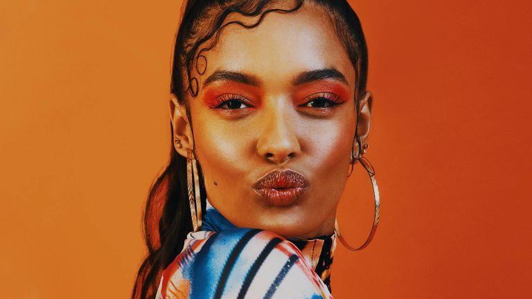 Shot of a young woman posing with colorful eyeshadow against a orange background with a trendy hairstyle