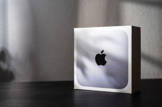 Mac Mini in its packaging on a desk.