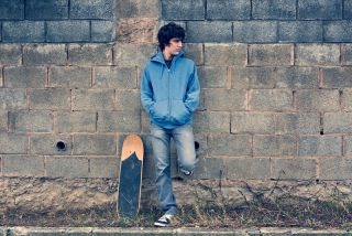 A teen boy stands against a wall, alone.