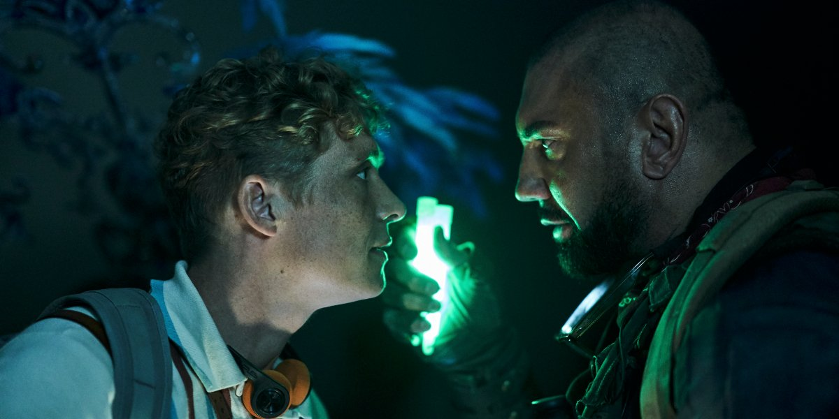 Matthias Schweighöfer and Dave Bautista talk by the light of glow stick in Army of the Dead.