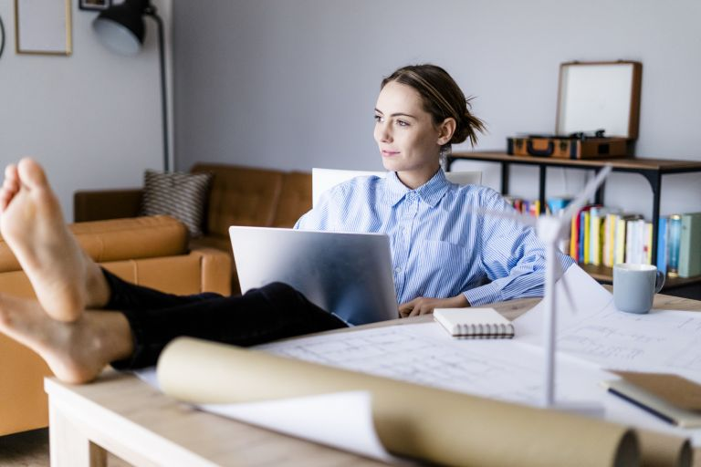 Woman in office working on laptop with feet on table, benefits of working from home