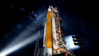 An artist's illustration of NASA's massive Space Launch System rocket and its Orion capsule on the launchpad.