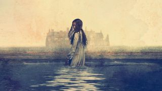 A faceless woman stands in the waters of a lake in front of a large stately home