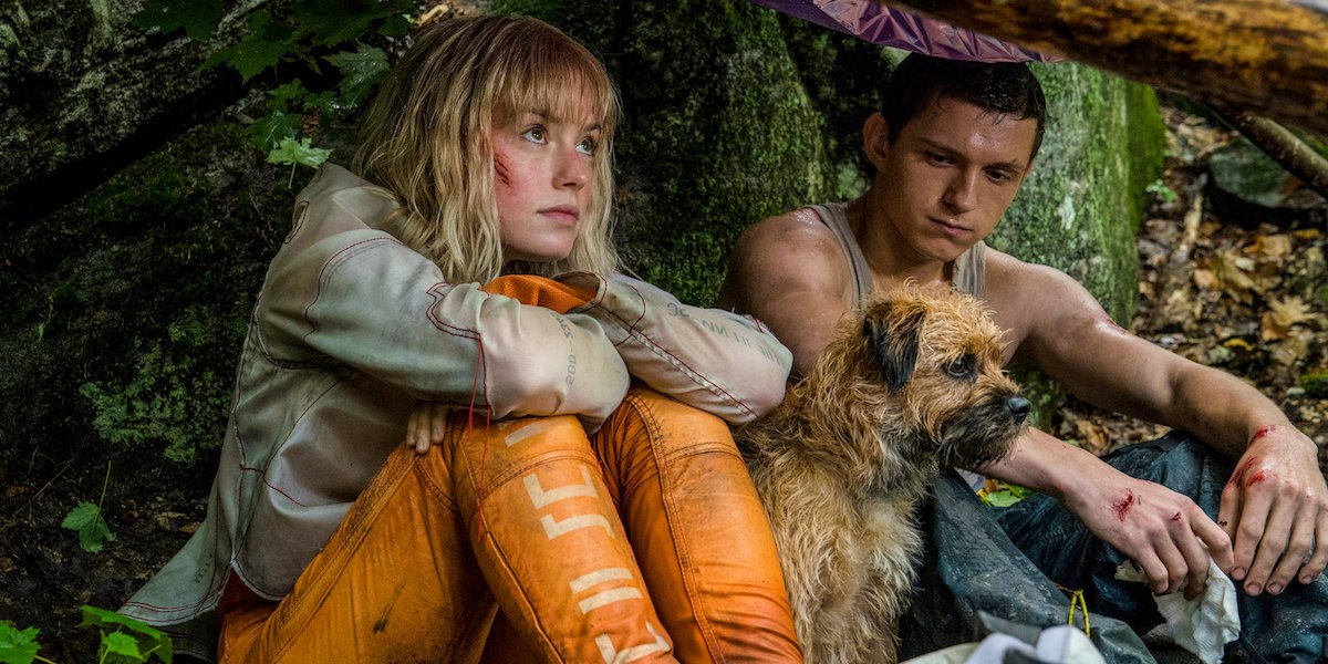 Daisy Ridley and Tom Holland in Chaos Walking sitting under some shelter with a pup named Manchee