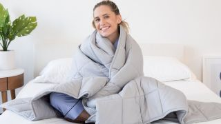 The best weighted blankets in 2021: A woman with blonde hair sits on her bed wrapped in a Luna Adult Weighted Blanket