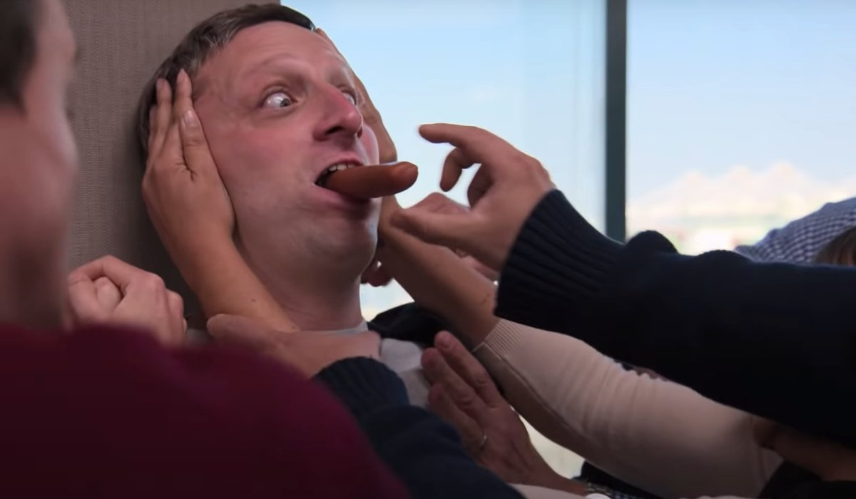 Tim Robinson is surrounded by a crowd trying to snag a hot dog from his mouth in I Think You Should Leave.