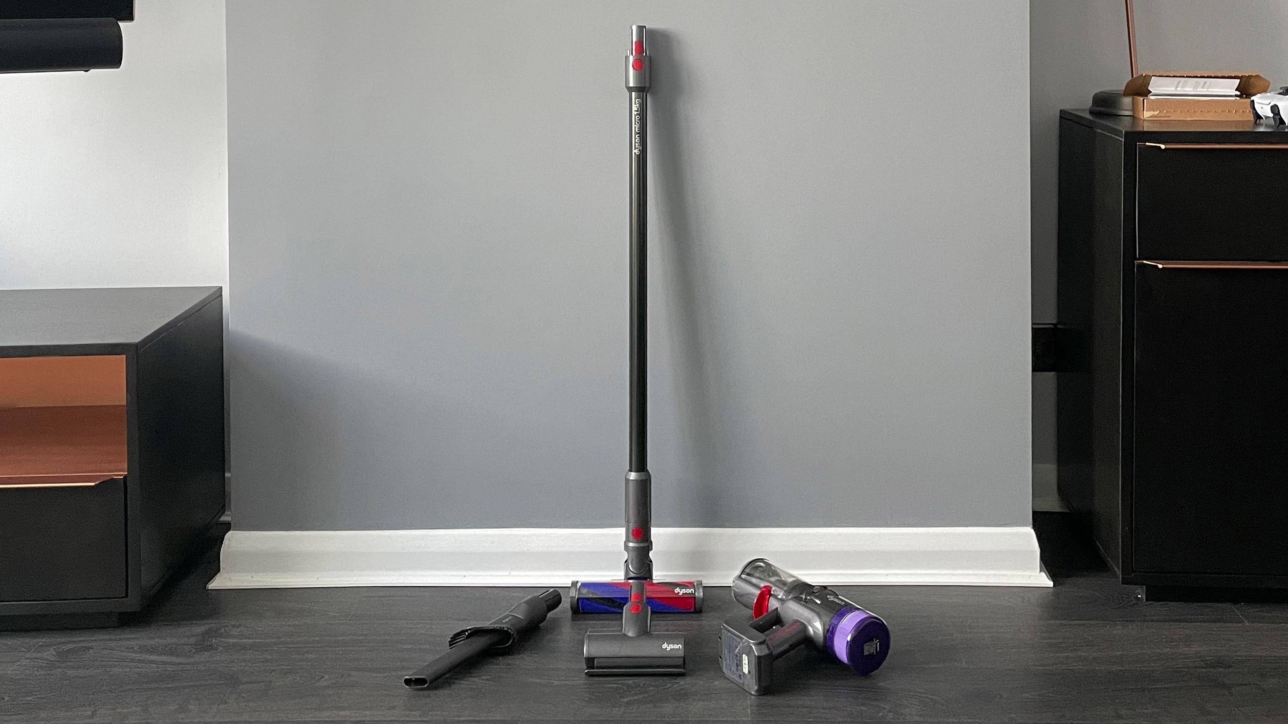 The Dyson Micro 1.5kg and its attachements leaning against a wall
