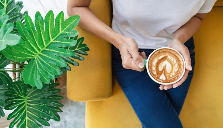 njoying fresh coffee. Top view of beautiful young woman holding cup while relaxing on sofa at home - stock photo