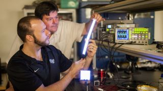 Wake Forest PhD student Greg Smith (left) and lead researcher David Carroll light up a FIPEL bulb