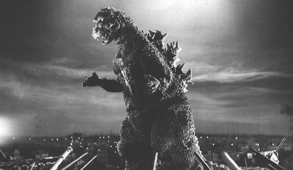 Godzilla looming over a human city