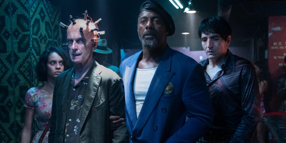 Daniela Melchior, Peter Capaldi, Idris Elba, and David Dastmalchian walk into a club in The Suicide Squad.