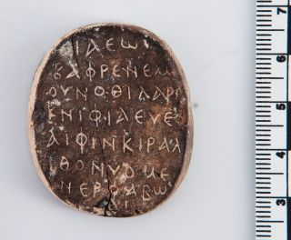 The inscription side of the amulet contains a Greek inscription.