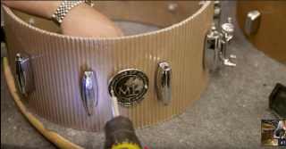 Cardboard snare drum being fitted with hardware by Masters Of Maple
