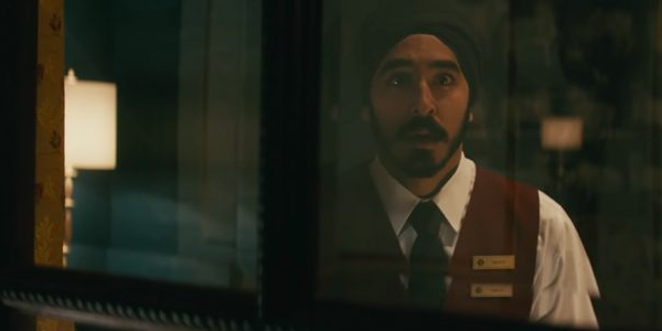 Hotel Mumbai Dev Patel looks out a window with a concerned face