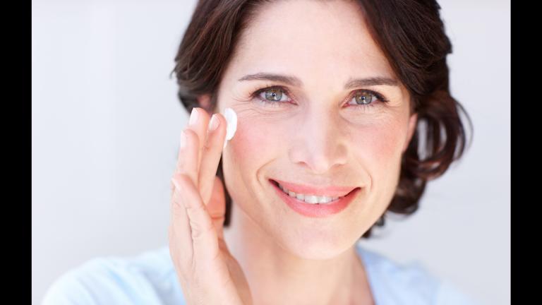 Woman smiling and applying eye cream