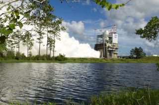 Steam billows out of a NASA structure with a body of water in the foreground