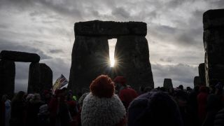 People look toward the sun at Stonehenge, as they take part in a winter solstice ceremony at the ancient neolithic monument in England.