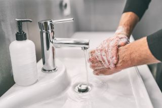 A person washing their hands with soap.