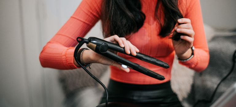 Woman using hair straightener at home