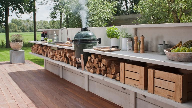 outdoor kitchen set up with wooden floor and steel top surfaces by garden house design