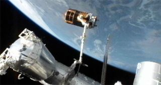 Japan's unmanned HTV-3 cargo ship is perched at the end of the International Space Station's robotic arm before its release on Sept. 12, 2012
