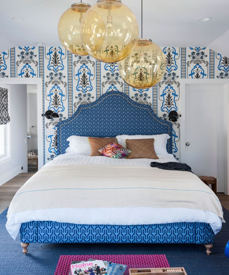 Blue bedroom ideas with blue patterned wallpaper and headboard, large round glass ceiling lights and white bedlinen.