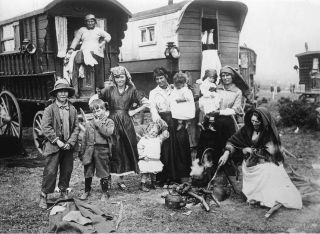 A black and white photo of a Roma camp and wagon on the beach in England