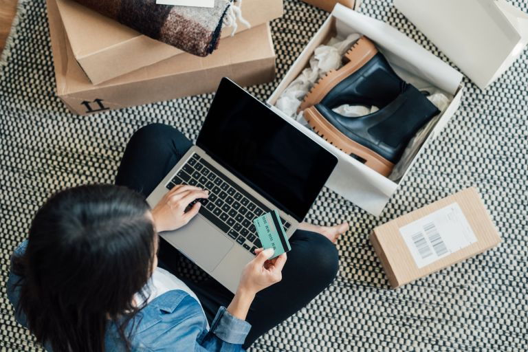 High angle view of a young Asian woman shopping online on laptop, making payment with credit card. Enjoying Seasonal sales