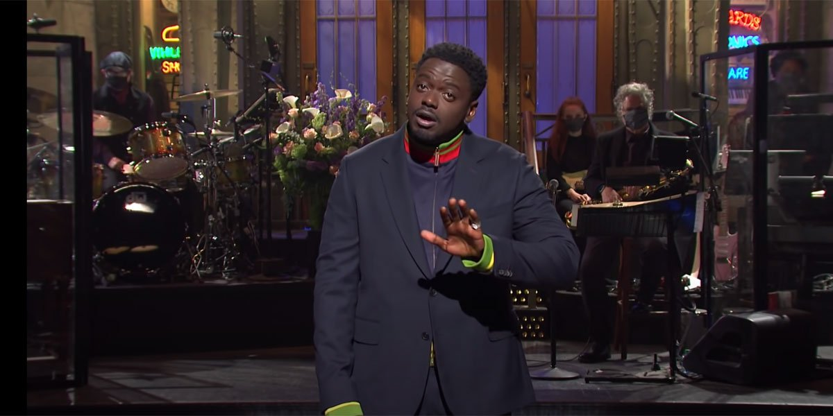 Daniel Kaluuya in a blue suit with green accents on the Saturday Night Live stage about to make a joke.