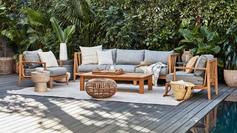 A teak wood outdoor sofa and chair set in a backyard with lush tropical foliage
